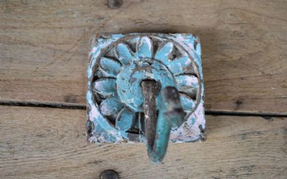 Old wooden hook with floral carvings and blue paint tones